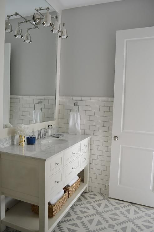 White and gray bathroom features top half of walls painted gray .