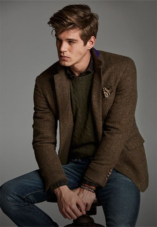 Man layers brown herringbone blazer over green cable-knit sweater .