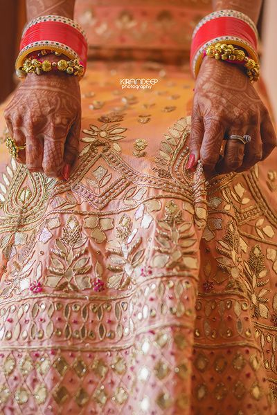 Peach lehenga with gota Patti work being held by bride (With .