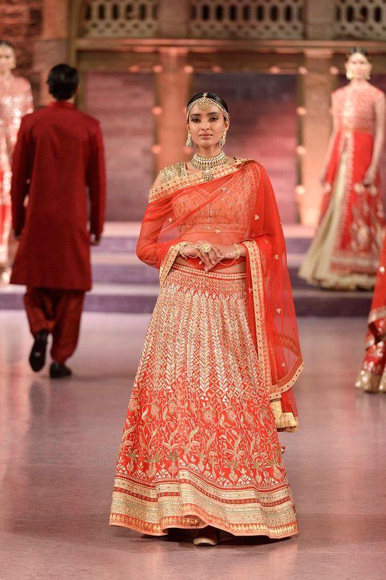 Heavily embroidered red gota patti and zardosi raw silk lehenga .