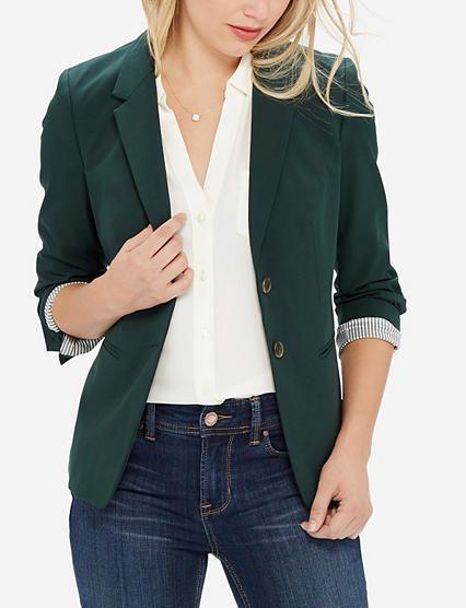 Women's dark green blazer over dark wash jeans and white collared .