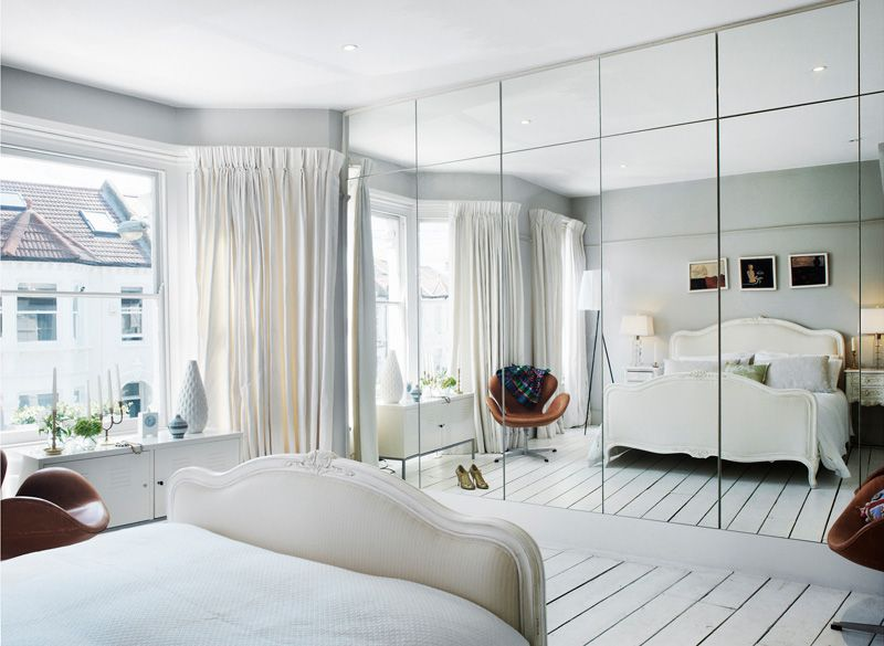 Wall of mirrored closets, wardrobes, storage. Reflects the light .