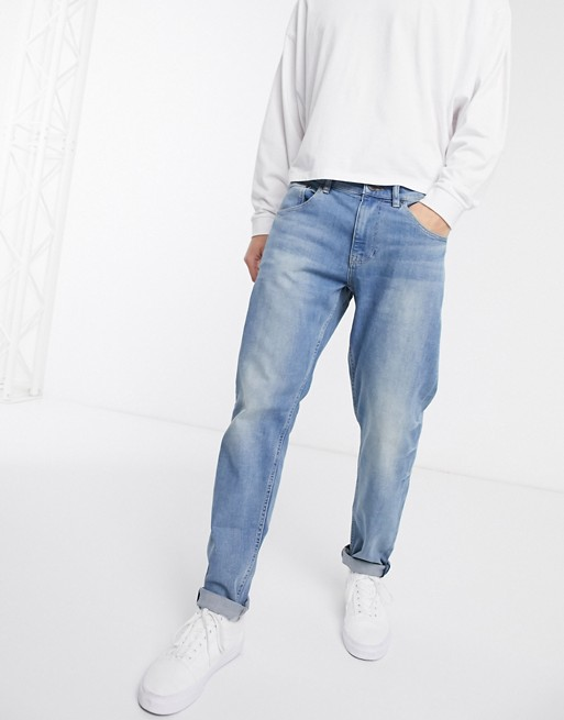ASOS DESIGN stretch tapered jeans in mid wash blue | AS