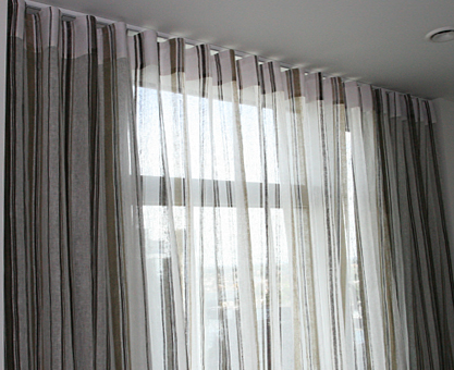 Sheer voile curtains with Ripplefold heading and blackout curtains .