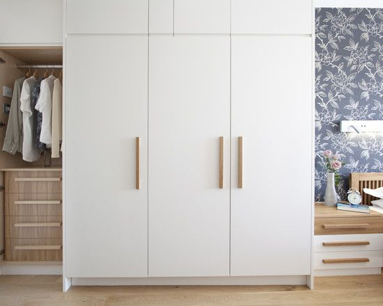 Clean white wardrobe with wooden handles | Bedroom cupboard .